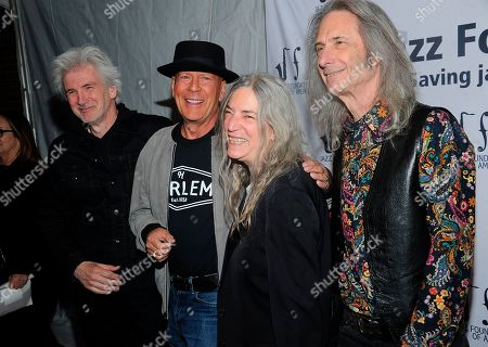 """Stock Image of Tony Shanahan; Patti Smith;Lenny Kaye; Bruce Willis. Tony Shanahan, Left,Bruce Willis, second left Patti Smith, center and Lenny Kaye walk the red carpet at the Jazz Foundation of America's 17th annual """"A Great Night In Harlem"""" gala concert at The Apollo Theater, in New York"""