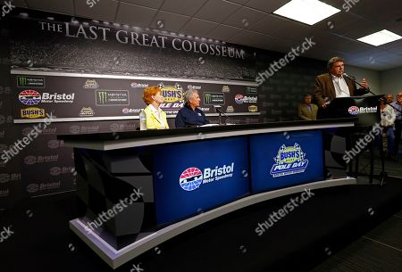 Hall of Fame driver and FOX television announcer Darrell Waltrip, center, and his wife, Stevie, listen as Mike Helton, NASCAR vice-president, speaks to media during a press conference announcing Waltrip's retirement from the booth before practice for a NASCAR Cup Series auto race, in Bristol, Tenn