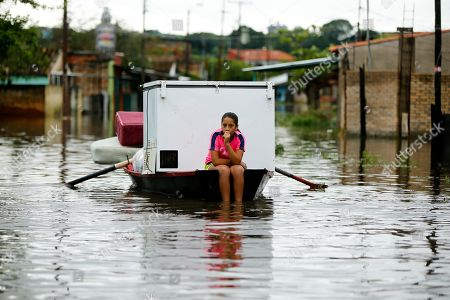 Carolina Vera, 13, rides on a boat through a flooded street in the Villa Colorada neighborhood, in Asuncion, Paraguay, . More than 20,000 people in Paraguay have been evacuated after torrential rains caused extensive flooding