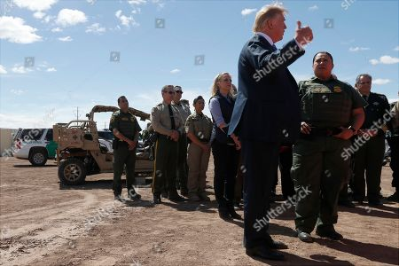 President Donald Trump visits a new section of the border wall with Mexico in Calexico, Calif., . Gloria Chavez with the U.S. Border Patrol, third from right, and Homeland Security Secretary Kirstjen Nielsen listen
