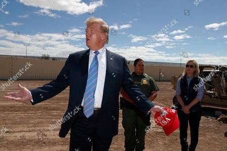 President Donald Trump visits a new section of the border wall with Mexico in Calexico, Calif., . Gloria Chavez with the U.S. Border Patrol, center, and Homeland Security Secretary Kirstjen Nielsen listen