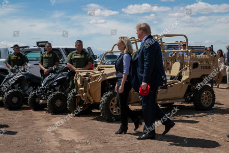 President Donald Trump walks with Homeland Security Secretary Kirstjen Nielsen as they visit a newly constructed part of a border wall with Mexico in Calexico, Calif