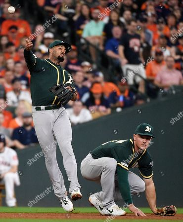 Oakland Athletics shortstop Marcus Semien, left, throws out Houston Astros' Robinson Chirinos as third baseman Matt Chapman, right, watches during the sixth inning of a baseball game, in Houston