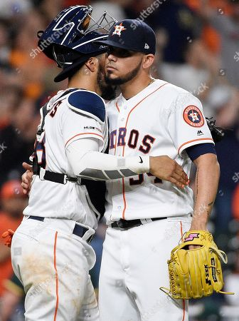 Houston Astros relief pitcher Roberto Osuna, right, hugs catcher Robinson Chirinos after their win over the Oakland Athletics in a baseball game, in Houston