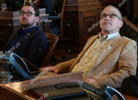 Kansas state Reps. Blake Carpenter, left, R-Derby, and Bradley Ralph, R-Dodge City, watch an electronic tally board as the House approves an anti-abortion bill that they favor, at the Statehouse in Topeka, Kansas. The bill would require abortion providers to tell patients that medication abortions can be reversed after they take the first of two pills