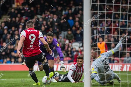 Neal Maupay (Brentford) moves forward to get the ball released by Kelle Roos (GK)(Derby County) who then regains hold of the ball assisted by Richard Keogh (Capt)(Derby County) watched by Oliver Watkins (Brentford) during the EFL Sky Bet Championship match between Brentford and Derby County at Griffin Park, London