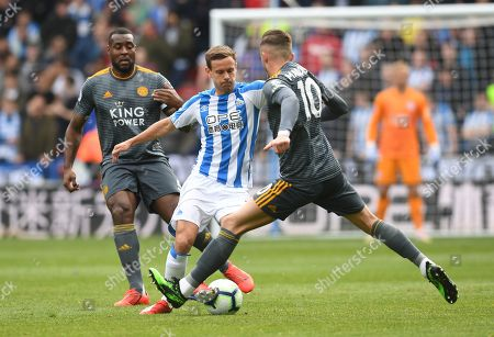 Stock Photo of Chris Lowe of Huddersfield Town between Wes Morgan and James Maddison of Leicester City