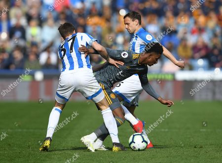 Demarai Gray of Leicester City between Eric Durm and Chris Lowe of Huddersfield Town