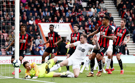Asmir Begovic of Bournemouth pushes a shot wide from Ashley Barnes of Burnley.