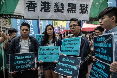 Stock Picture of Ivan Lam (R-2), chairman of pro-democratic party Demonstrator, alongside Joshua Wong, holding placards in different languages protesting against the new law proposals.