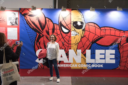 A woman posing for a picture in front of a poster by Stan Lee. Celebration of the comic lounge 37, numerous exhibitors meet and held different conferences, around 118,000 people gathered during the last edition, where the influx of more people was expected by enlarging the surface of the exhibition.
