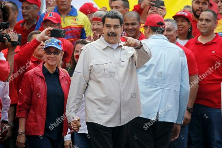Holding hands with his wife, Cilia Flores, Venezuela's President Nicolas Maduro points at supporters gathering in support of his government at the Miraflores presidential palace in Caracas, Venezuela, . Rival political factions are taking the streets across Venezuela in a mounting struggle for control of the crisis-wracked nation recently hit by crippling blackouts