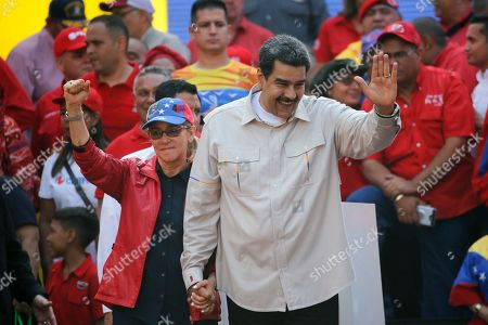 Venezuela's President Nicolas Maduro, right, and his wife Cilia Flores, wave to supporters gathering at the Miraflores presidential palace in Caracas, Venezuela, . Rival political factions are taking the streets across Venezuela in a mounting struggle for control of the crisis-wracked nation recently hit by crippling blackouts