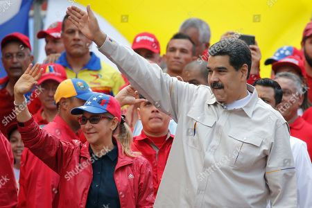 Venezuela's President Nicolas Maduro, right, and his wife Cilia Flores wave to backers that marched in support of his government to the presidential palace in Caracas, Venezuela, . Rival political factions are taking the streets across Venezuela in a mounting struggle for control of the crisis-wracked nation recently hit by crippling blackouts
