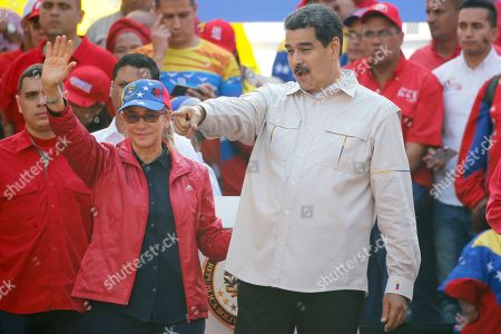 Venezuela's President Nicolas Maduro, right, and his wife Cilia Flores wave to supporters rallying at the presidential palace in Caracas, Venezuela, . Rival political factions are taking the streets across Venezuela in a mounting struggle for control of the crisis-wracked nation recently hit by crippling blackouts