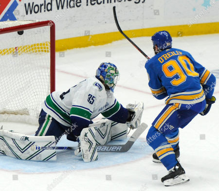 St. Louis Blues' Ryan O'Reilly (90) scores in a shootout against Vancouver Canucks' Thatcher Demko (35) in an NHL hockey game, in St. Louis