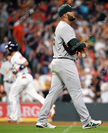 Oakland Athletics relief pitcher Yusmeiro Petit, right, walks away from the mound as Houston Astros' Robinson Chirinos, back left, rounds the bases on a solo home run during the sixth inning of a baseball game, in Houston