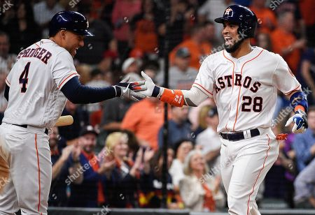 Houston Astros' Robinson Chirinos (28) celebrates his solo home run off Oakland Athletics relief pitcher Yusmeiro Petit with George Springer during the sixth inning of a baseball game, in Houston