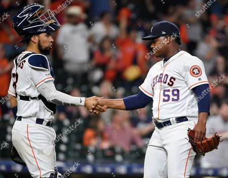 Houston Astros relief pitcher Framber Valdez (59) shakes hands with catcher Robinson Chirinos after their win over the Oakland Athletics in a baseball game, in Houston
