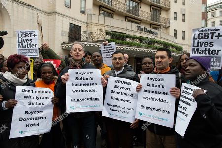 Activist Peter Tatchell (left) and other protesters are seen holding placards outside the Dorchester Hotel during the Protest. Protesters gathered outside Dorchester Hotel in London, UK which is owned by the Sultan of Brunei Hassanal Bolkia, to protest and condemn the new anti-LGBT laws brought in by Sultan. Under the new laws introduced in Brunei those found guilty of gay sex or adultery could be stoned to death. Some celebrity's in the world have voiced opposition to the regime and condemn the new laws and called for a boycott of hotels owned by sultan.