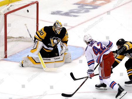 New York Rangers' Brendan Smith (42) scores against Pittsburgh Penguins goaltender Matt Murray (30) with Jack Johnson defending during the first period of an NHL hockey game in Pittsburgh