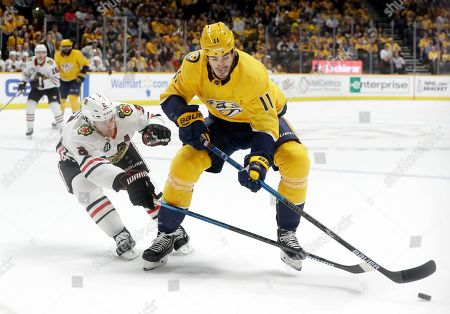 Duncan Keith, Brian Boyle. Chicago Blackhawks' Duncan Keith (2) and Nashville Predators' Brian Boyle (11) reach for the puck in the second period of an NHL hockey game, in Nashville, Tenn