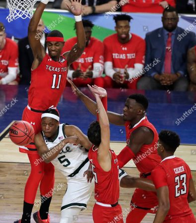Michigan State guard Cassius Winston (5) passes the ball in front of Texas Tech forward Tariq Owens (11) during the first half in the semifinals of the Final Four NCAA college basketball tournament, in Minneapolis