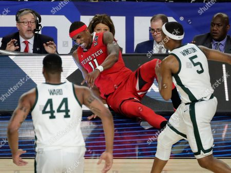 Texas Tech forward Tariq Owens (11) lands on the scorers table while trying to save a ball from going out of bounds in front of Michigan State's Nick Ward (44) and Cassius Winston (5) during the first half in the semifinals of the Final Four NCAA college basketball tournament, in Minneapolis