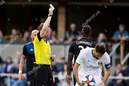 Referee Drew Fischer, left, give San Jose Earthquakes defender Harold Cummings a yellow card in the second half of an MLS soccer match against the Portland Timbers on in San Jose, Calif. The Earthquakes won 3-0