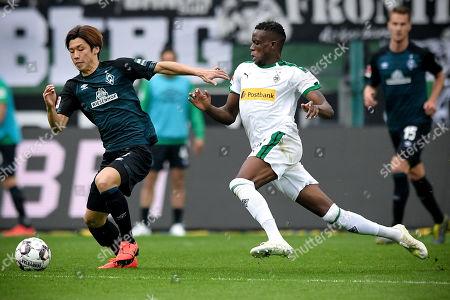 Bremen's Yuya Osako (L) in action against Moenchengladbach's Denis Zakaria (R) during the German Bundesliga soccer match between Borussia Moenchengladbach and Werder Bremen at Borussia-Park in Moenchengladbach, Germany, 07 April 2019.