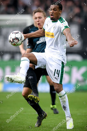Moenchengladbach's Alassane Plea (R) in action against Bremen's Ludwig Augustinsson (L) during the German Bundesliga soccer match between Borussia Moenchengladbach and Werder Bremen at Borussia-Park in Moenchengladbach, Germany, 07 April 2019.
