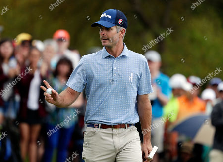 Stock Photo of Kevin Streelman waves after making a birdie putt on the 16th hole during the final round of the Texas Open golf tournament, in San Antonio