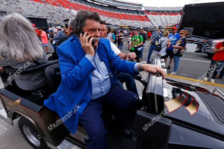 Stock Image of Mike Helton, NASCAR vice-chairman, rides through the pit area before a NASCAR Cup Series auto race, in Bristol, Tenn