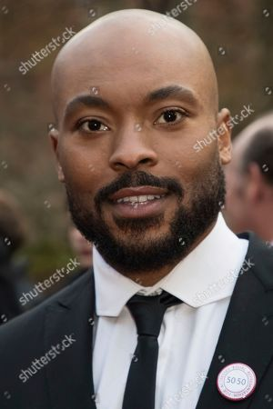 Arinze Kene poses for photographers upon arrival at the Olivier Awards in London