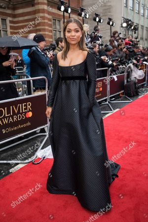 Antonia Thomas poses for photographers upon arrival at the Olivier Awards in London