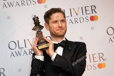 Kyle Soller poses for photographers backstage with his Best Actor award for his role in the play 'The Inheritance at the Olivier Awards in London