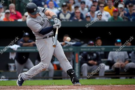 New York Yankees' Luke Voit hits a single in the ninth inning of the team's baseball game against the Baltimore Orioles, in Baltimore