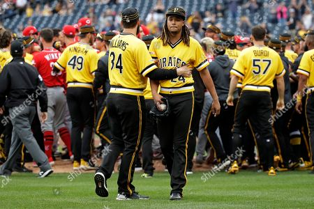 Pittsburgh Pirates starting pitcher Chris Archer (24) walks away from a bench clearing with fellow pitcher Trevor Williams (34) during the fourth inning of a baseball game in Pittsburgh, . A wild pitch by Archer during an at-bat by Reds' Derek Dietrich started the fracas
