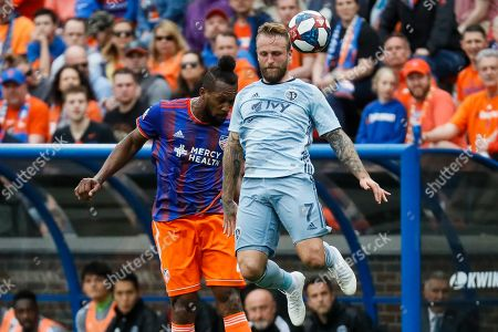 Johnny Russell, Kendall Waston. Sporting Kansas City forward Johnny Russell (7) heads the ball against FC Cincinnati defender Kendall Waston, left, in the second half of an MLS soccer match, in Cincinnati