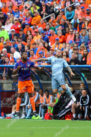 FC Cincinnati's Kendall Waston (left) goes up for a header against Sporting KC's Johnny Russell (right) during an MLS soccer game between FC Cincinnati and Sporting Kansas City at Nippert Stadium in Cincinnati, Ohio