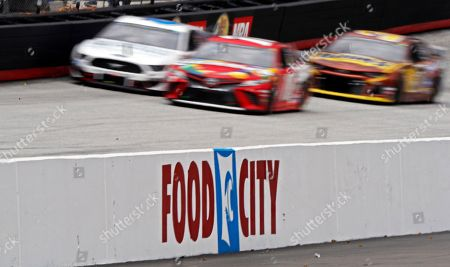 Stock Photo of Kyle Busch, center, leads Aric Almirola (10) and Ryan Newman (6) down the back stretch during the NASCAR Cup Series auto race, at Bristol Motor Speedway in Bristol, Tenn