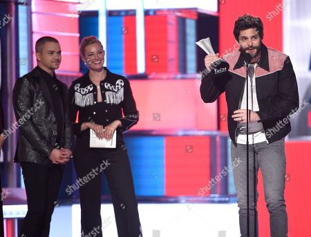 Thomas Rhett, Hunter Hayes, Beth Behrs. Thomas Rhett, right, accepts the award for male artist of the year as from left, presenters Hunter Hayes and Beth Behrs look on at the 54th annual Academy of Country Music Awards at the MGM Grand Garden Arena, in Las Vegas
