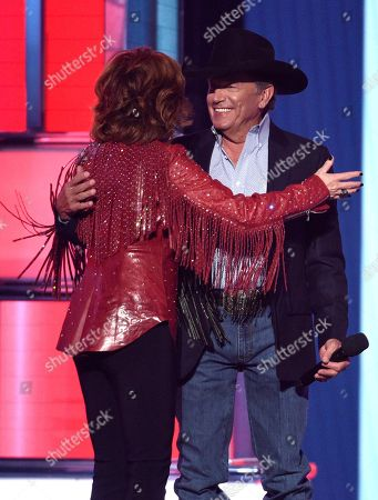 Reba McEntire, George Strait. Reba McEntire, left, greets George Strait as he walks onstage to present the Dick Clark artist of the decade award at the 54th annual Academy of Country Music Awards at the MGM Grand Garden Arena, in Las Vegas