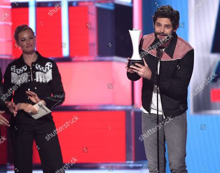 Thomas Rhett, Beth Behrs. Thomas Rhett, right, accepts the award for male artist of the year as from left, presenter Beth Behrs looks on at the 54th annual Academy of Country Music Awards at the MGM Grand Garden Arena, in Las Vegas