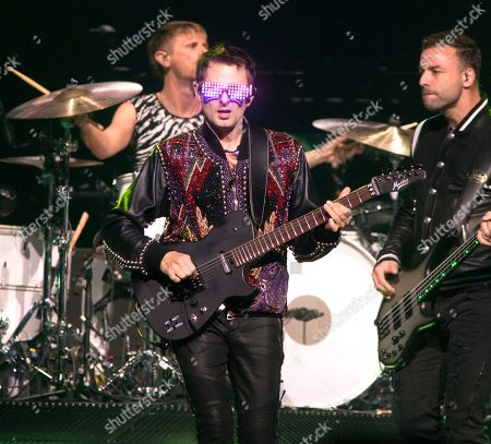 """Dominic Howard, Matt Bellamy, Chris Wolstenholme. Dominic Howard, drummer, Matt Bellamy, center, and Chris Wolstenholme of the band Muse perform in concert during their """"Simulation Theory World Tour"""" at The Wells Fargo Center, in Philadelphia"""