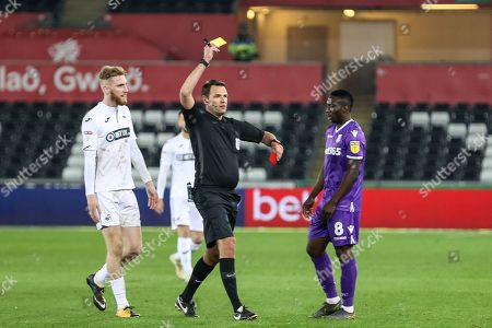 Stock Image of Referee James Linington issues Tom Edwards of Stoke City  a second yellow card