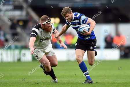 Rhys Priestland of Bath Rugby fends Jake Woolmore of Bristol Bears