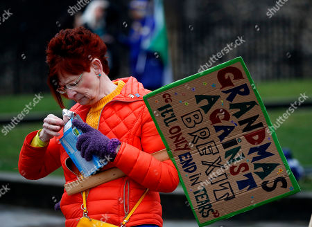 A pro EU protestor gets a snack, while protesting opposite the Houses of Parliament in London, . Britain's government and opposition party are hoping to find an acceptable compromise Brexit deal, ahead of further talks with European Union leaders later this week