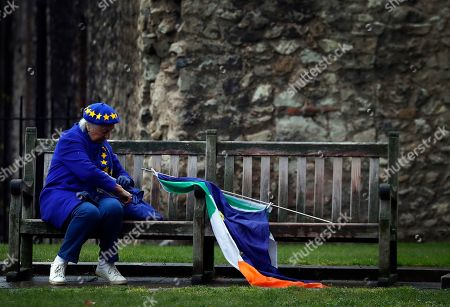 A pro EU protestor takes a rest on a bench opposite the Houses of Parliament in London, . Britain's government and opposition party are hoping to find an acceptable compromise Brexit deal, ahead of further talks with European Union leaders later this week