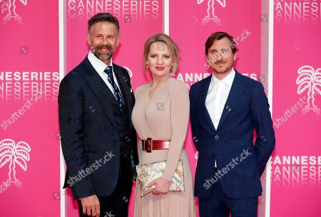 Stock Photo of Cast members of 'The Twelve', Belgian actors Johan Heldenbergh (L), Maaike Cafmeyer (C) and Belgian producer Wouter Bouvijn (R) pose on the pink carpet during the Cannes Series Festival in Cannes, 08 April 2019. The event will take place from 05 to 10 April.